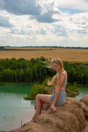 A blonde girl is sitting on the top of a hill above an unusual lake. The wind blows her hair. Stockfoto