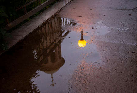 A bright yellow lantern, part of the temple and openwork railing are reflected in a rain puddle on the asphalt in the evening.