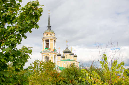 A bright yellow Church with a sharp spire against a cloudy sky, photographed through the branches of trees.