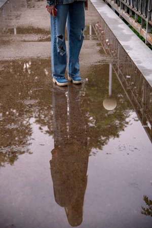 A teenage girl with a phone in her hand stands on the asphalt, reflected in a puddle.