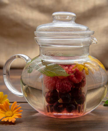 Transparent teapot with different colored berries inside. Fruit tea with mint leaves.