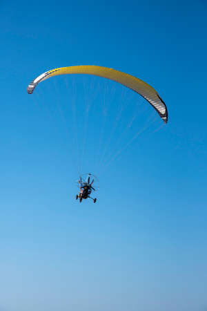 A paraglider with a bright yellow parachute against a clear blue sky. Stockfoto
