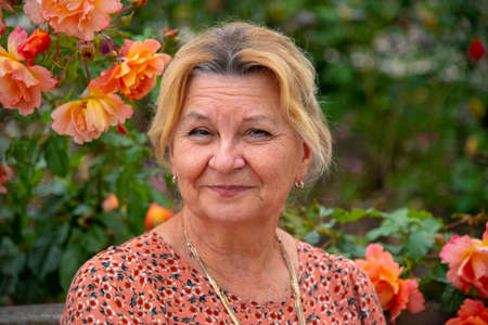 Portrait of an elderly wrinkled woman 67 years old on a background of rose flowers. Stockfoto