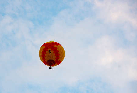 A bright orange-red balloon against a blue cloudy sky.