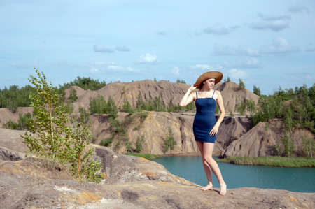 A young girl with blonde hair, wearing a denim sundress stands on a high hill above a blue lake.