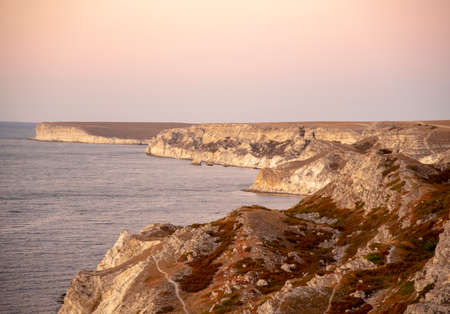 Gentle sunset over the sea and rocky relief coast. Summer evening seascape. Stockfoto