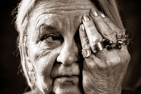 Tinted monochrome Portrait of an elderly woman with many wrinkles. The woman covers one eye with her hand.