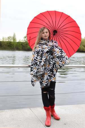 A girl with blonde hair in red rubber boots and a rain coat stands under a red umbrella on the embankment.