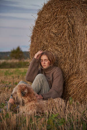 A beautiful sad blonde girl and a dog are sitting in a field.