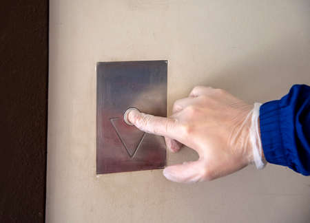 A man's hand in a rubber glove, pressing the button to call the Elevator. Protective measures in the event of a pandemic.