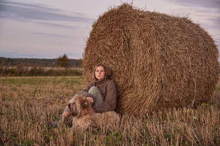 A beautiful sad blonde girl and a dog are sitting in a field, leaning against a haystack.