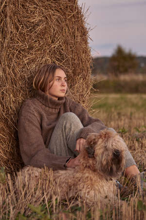 A blonde girl in a warm knitted sweater and a dog sit next to a haystack in the evening.