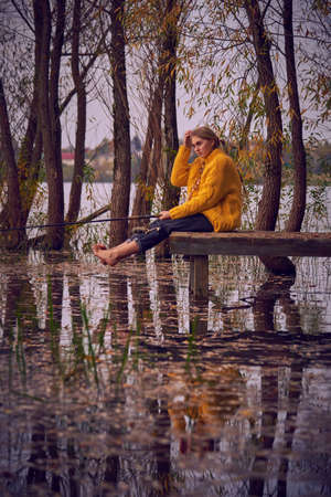 A young girl in a yellow sweater sits on the bridge over the lake and catches fish. Early autumn landscape.