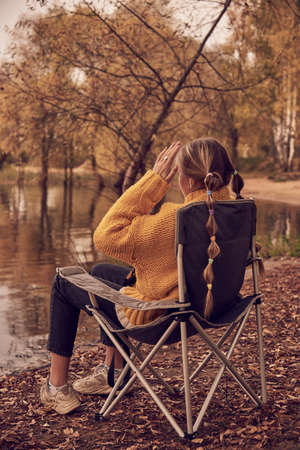 A teenage girl in a bright yellow sweater is sitting in a camp chair on the shore of a lake on an autumn evening.