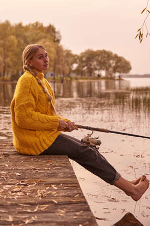 A girl with pigtails in a bright yellow knitted sweater sits on a wooden bridge over the lake and catches fish.