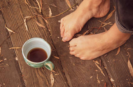 Women's bare feet stand on a wooden floor covered with autumn leaves. A ceramic Cup with a drink stands next to the feet.