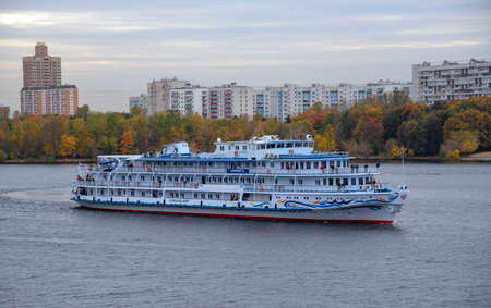 Russia, Moscow, October 2020. A cruise ship sails along the Moscow river against the background of autumn trees and high-rise residential buildings.