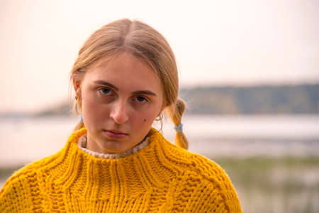 Facial portrait of a blonde girl in a bright warm yellow sweater on a blurry background of nature.
