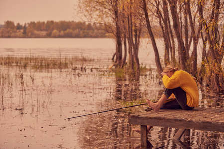 A barefoot Girl in a warm sweater sits with a fishing rod on a wooden bridge by the lake. Autumn evening landscape.