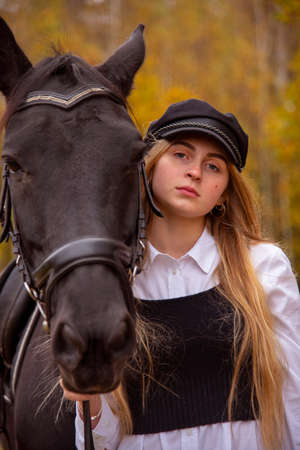 portrait of a girl with blonde hair, wearing a cap, and a Bay horse on the background of a forest.