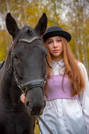Red-haired girl in a black hat with a Chestnut horse in the autumn forest. Stock Photo