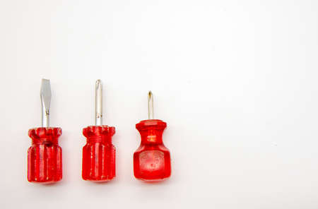 Three small screwdrivers with red plastic handles on a white background.