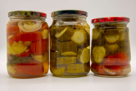 Three transparent jars with pickled vegetables, cucumbers, tomatoes and peppers, on a white background.