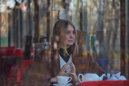 Slightly blurry portrait of a charming girl drinking tea, made through the window of a cafe. The window reflects the autumn Park.