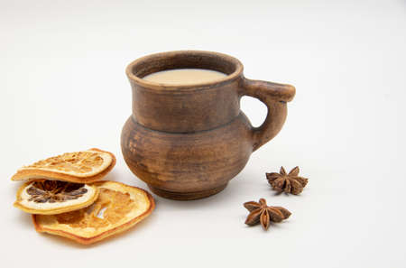 Brown clay mug and dried oranges on a white background. Imagens