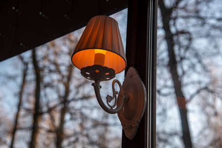 Burning vintage lamp on the window frame. Outside the window is an autumn Park. Stok Fotoğraf