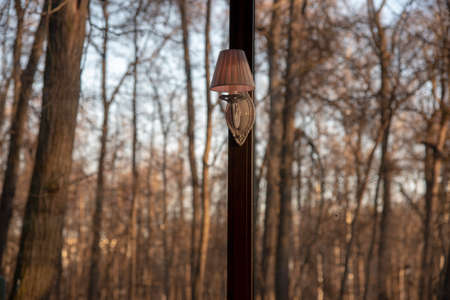 Lamp on the frame of the panoramic window, behind which the autumn Park with bare trees. Stok Fotoğraf