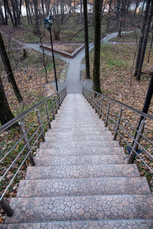 Long stone staircase with metal railing in autumn Park, top view.