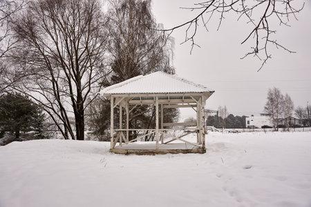 Wooden empty gazebo on the background of a winter landscape.
