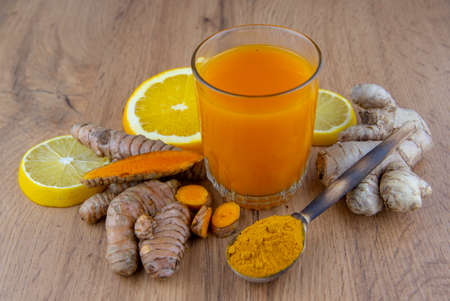 A glass of vitamin cocktail, fresh turmeric root, ginger and orange on a gray background. The concept of healthy eating, nutritional vitamin supplements.