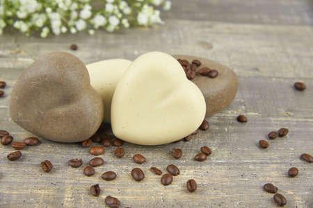 Fragrant coffee natural handmade soap in the shape of a heart and coffee beans on a wooden countertop.