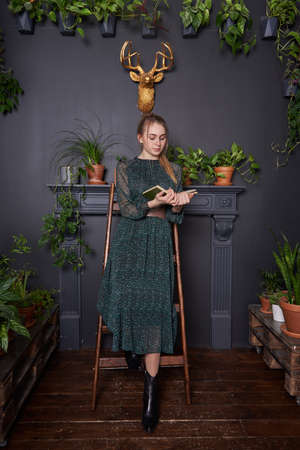 A blonde girl in a chiffon green dress with a book in hand on a wooden stepladder.