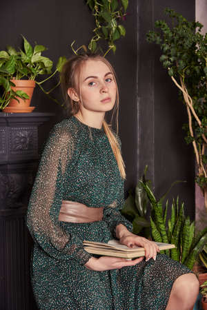 A blonde girl in a chiffon green dress with a book in hand in a cozy room.