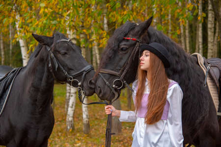 A red-haired slender girl stands in an autumn grove with two horses.