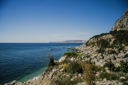 Bright blue sea and rocks and forest on a sunny day in the Crimea Stock Photo