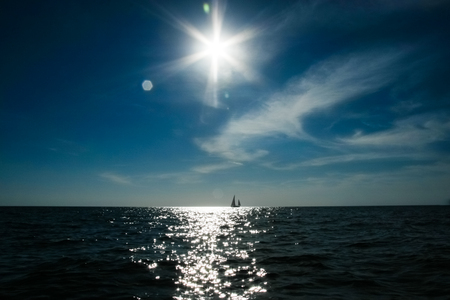 A lonely sail boat and the sun in the dramatic sky is sailing in the sea