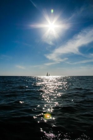 aloneness: A lonely sail boat and the sun in the dramatic sky is sailing in the sea
