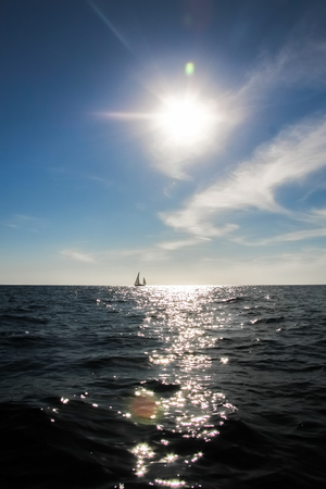 remoteness: A lonely sail boat and the sun in the dramatic sky is sailing in the sea