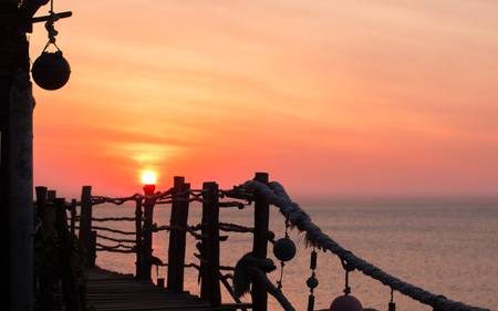 Sunrise or sunset at the tropical beach, sea at the background and party place at the foreground. Silhouette of the decorated fence Stock Photo
