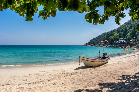 A boat at the white sand beach of the tropical blue sea. Daytime, Koh Phangan, Thailand Stock Photo