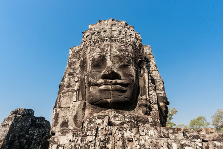 Ancient stone smiling face of the Prasat Bayon Wat temple in the jungle, Angkor wat, Cambodia. Angkor Wat isthe largest religious monument in the world.