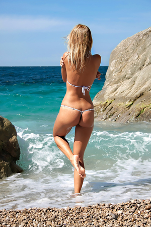 Rear view of a hot beautiful sun tanned blond long hair girl with sexy body and buttocks in white bikini getting ready to go into the sea. Summer sunny wild European beach.