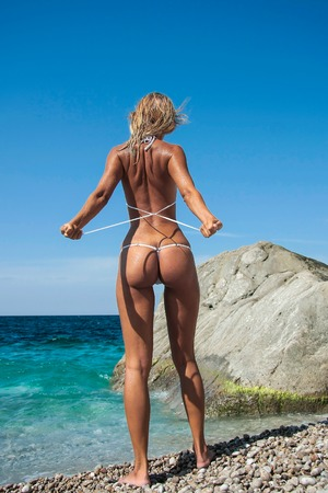 Rear view of a hot beautiful tanned girl with sexy body and buttocks in white bikini undressing to go into the sea. Summer sunny wild European beach. Crimea Stock Photo