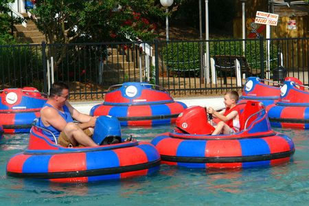 Man and Boy Keeping Cool with red and blue Bumper Boats Stock Photo - 1329019