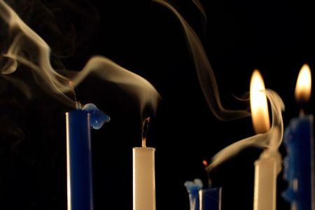 fünf Hanukkah Kerzen, zwei noch brennen und irgendwelche Rauchmakro, Fokus auf dem weißen, 2. vom links.