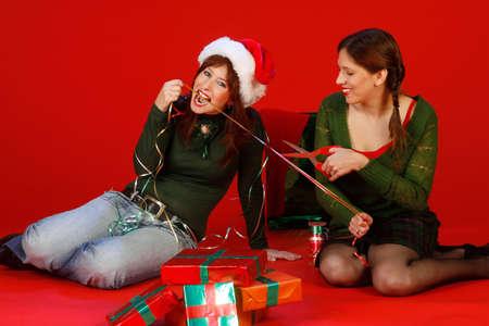 Dos mujeres j�venes, consiguiendo listas para Navidad